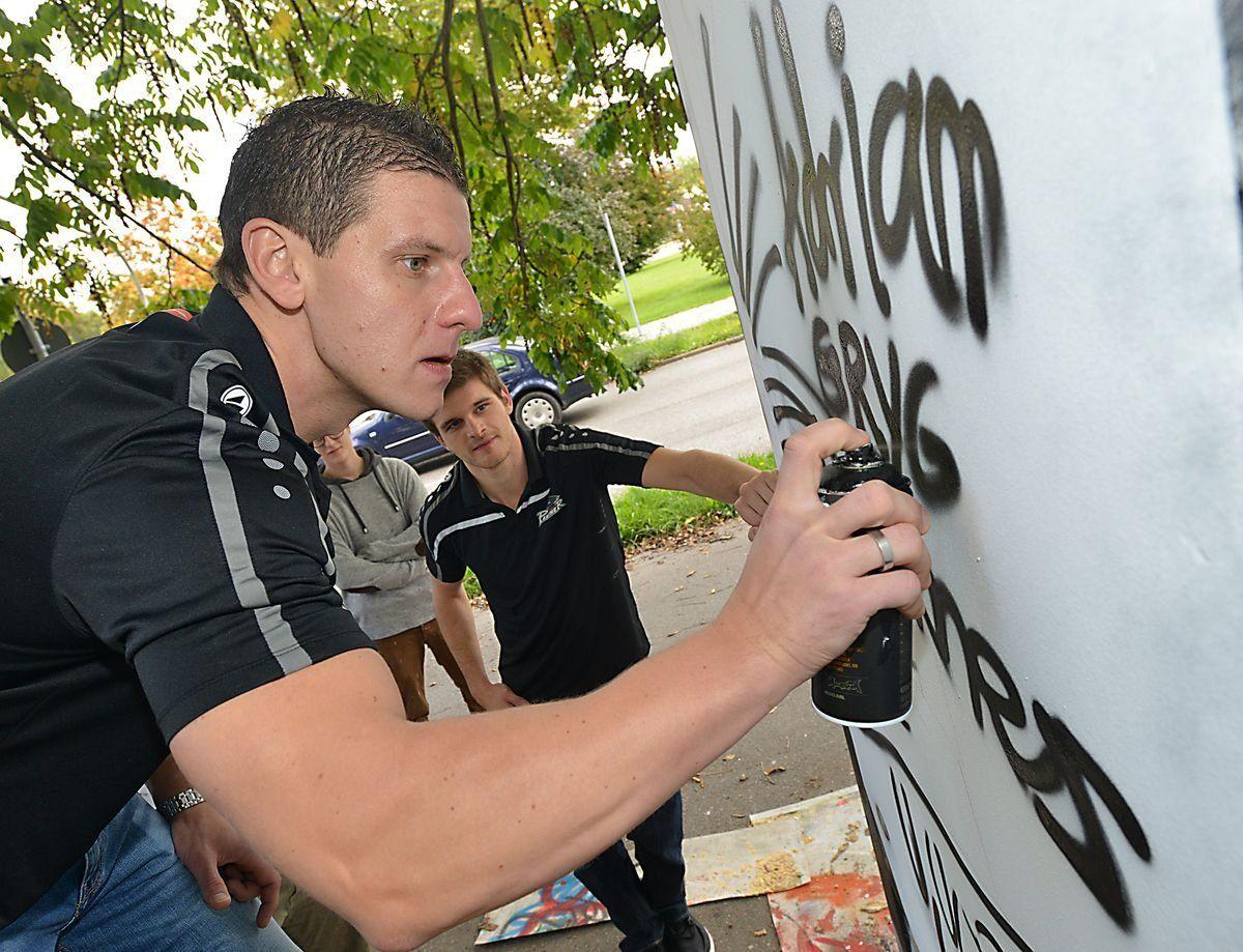 Adrian Grygiel verewigt sich auf dem Graffiti, beobachtet von Spieler-Kollegen James Bettauer. | Foto: swa / Thomas Hosemann
