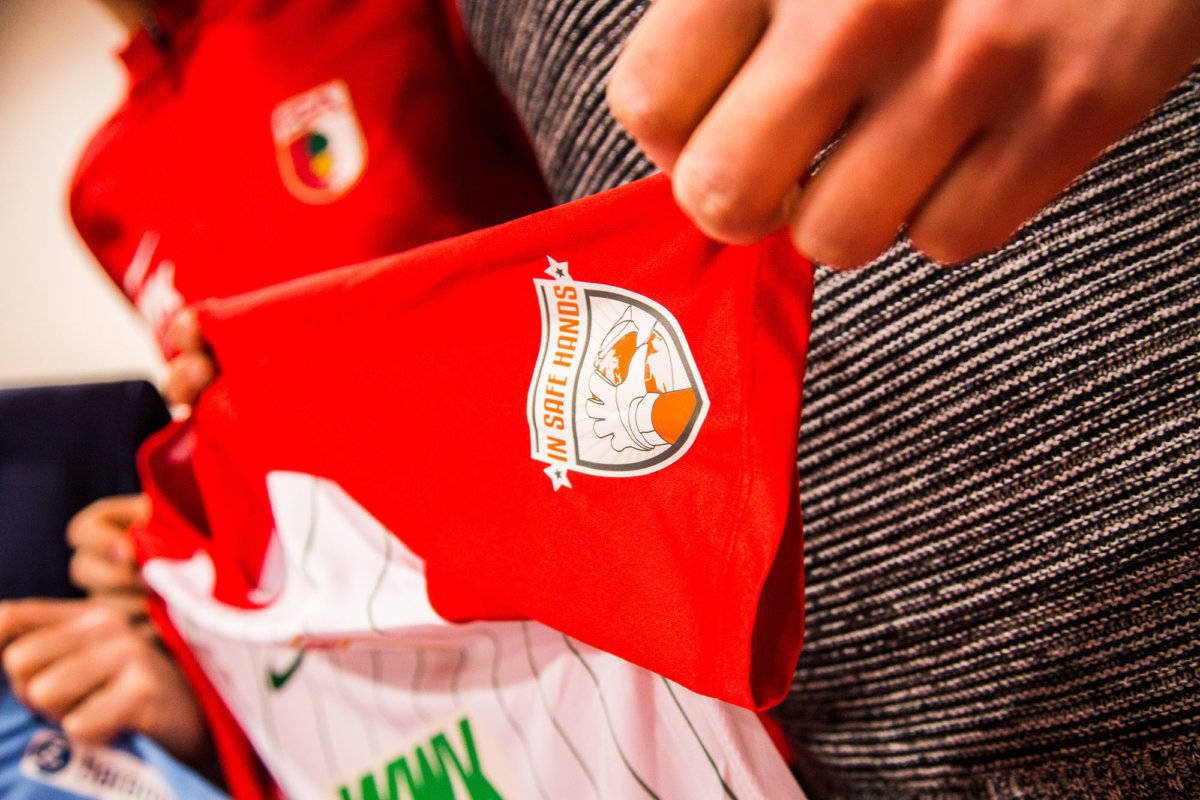 "20180315-FCA-mit-In-safe-Hands-e.V.-Logo-gegen-Bremen_021 Bremen-Spiel | Der FC Augsburg trägt ein besonderes Logo auf dem Trikot Augsburg Stadt FC Augsburg News Sport baramundi software AG FC Augsburg FCA Ingetrationsprojekt ""In safe hands e.V."" |Presse Augsburg"