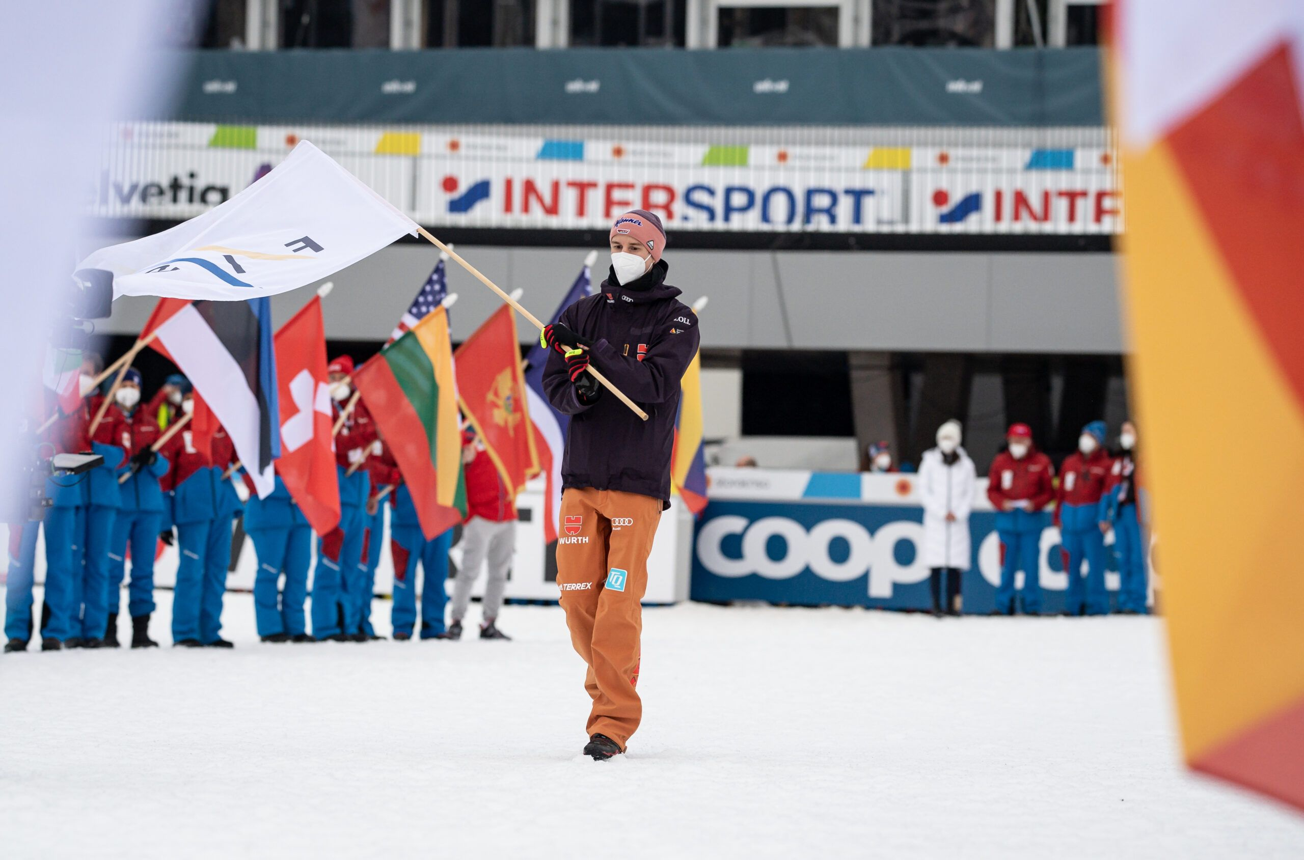 Arl Geiger Of Germany Carries The Fis Flag During The Closing Ceremony Scaled